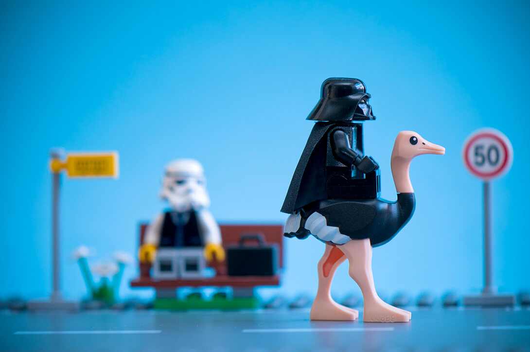 A Lego Darth Vader riding an ostrich on a road wiht a blurry stormtrooper masked man sitting on a bench
